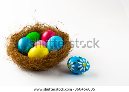 Multicolored Easter eggs in a nest and blue Easter egg with floral design on white background. Easter background. Easter symbol. Copy space - stock photo