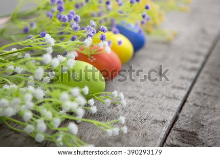Multicolored Easter eggs in fresh flowers. Easter background. Easter symbol. Easter hunt. Copy space - stock photo