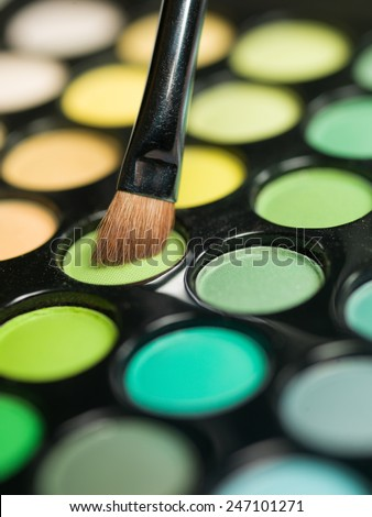 multicolored eyeshadow palette with makeup brush - stock photo
