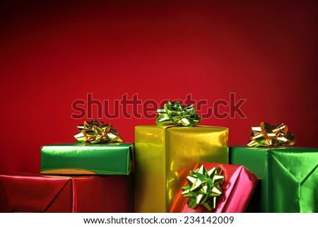 Multicolored gift boxes on red background - stock photo