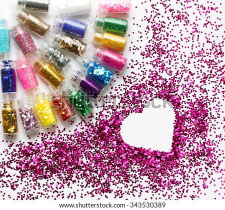 Multicolored glitter in bottles makeup, a place for text the form of heart. Beauty background. - stock photo