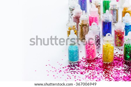 Multicolored glitter in bottles makeup, place for text. Beauty background - stock photo
