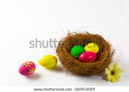 Multicolored hand decorated Easter eggs in a nest and yellow flower daisy on white background. Easter background. Easter symbol. Top view with copy space - stock photo