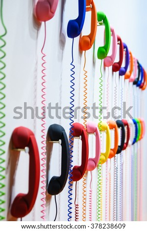 Multicolored handsets: yellow, blue, pink, green, red, white, orange hanging on a white wall. A spring wire spiral - stock photo