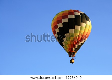 Multicolored hot air balloon in the blue sky. - stock photo