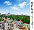 Multicolored houses among the green trees and blue sky. Panoramic view from the hill. Placed in Kiev, Ukraine almost in center of city. - stock photo