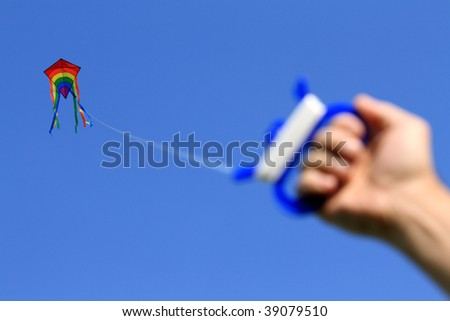 Multicolored kite high in clear blue sky, string holding in male hand, focused on kite - stock photo