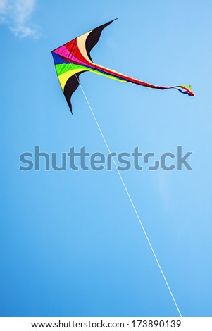 Multicolored kite with tail in clear blue sky