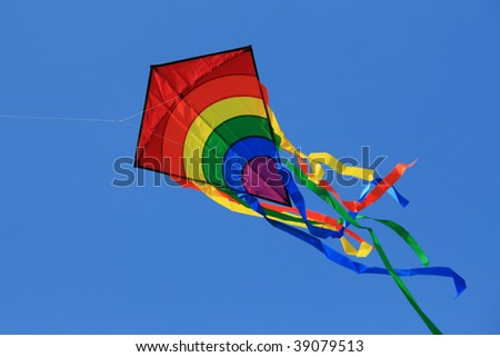 Multicolored kite with tail in clear blue sky - stock photo