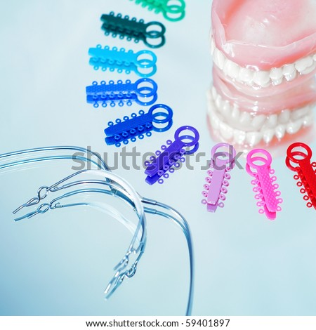 Multicolored ligature ties , prosthetic dentures and facebow - stock photo