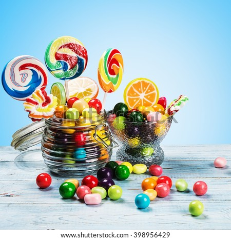 multicolored lollipops, candy and chewing gum in glass jar - stock photo