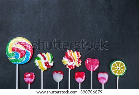 multicolored lollipops, candy and chewing gum on a black background. - stock photo