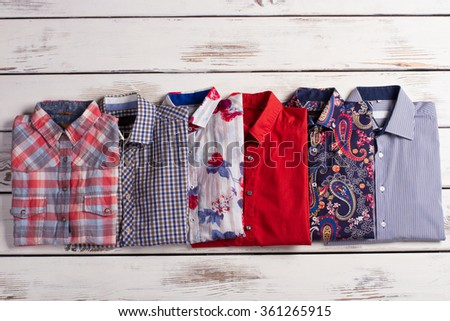 Multicolored men's shirts on a white wooden background. - stock photo