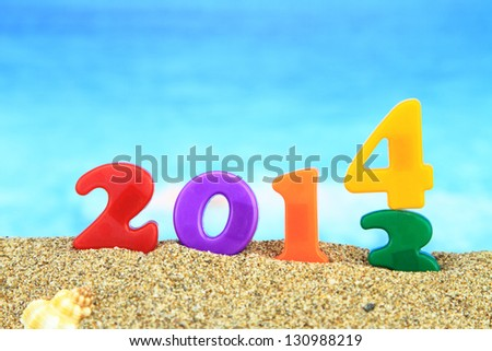Multicolored new year 2014 on the beach - stock photo