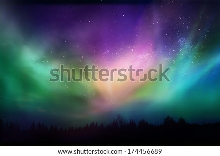 Multicolored northern lights (Aurora borealis)on Canadian forest - stock photo