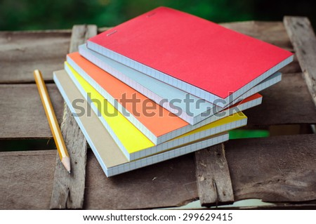 multicolored notepads with pen on brown wood table background
