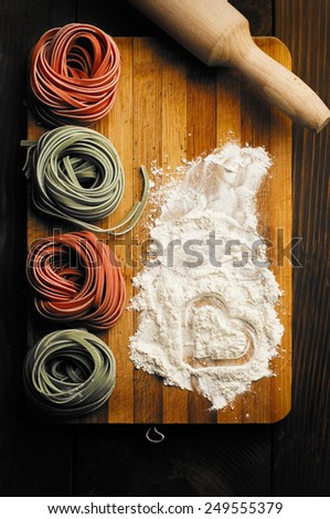 Multicolored pasta, egg, daugh roller and flour layer with heart shape - stock photo