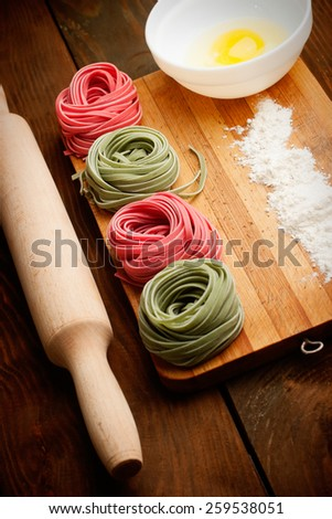 Multicolored pasta, egg yolk and daugh roller on wooden table - stock photo
