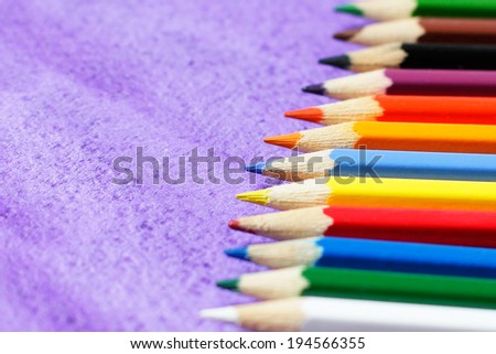 Multicolored pencils for drawing on violet background  - stock photo