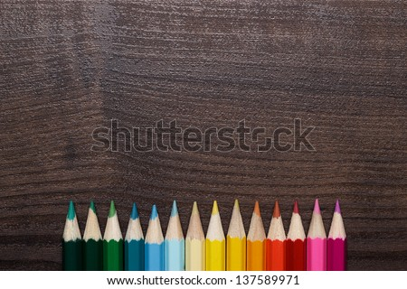 multicolored pencils on the brown wooden table - stock photo