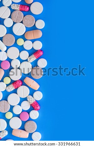 Multicolored pills on blue background close-up. Medical background with space for text. - stock photo