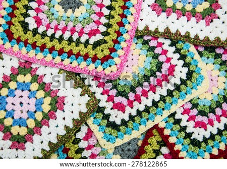 multicolored plaid squares of crocheted - close up - stock photo