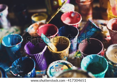 Multicolored plastic cans with paints. Artist workplace background. Art tools. Old dirty Paints background. Colorful artist palette. Soft toned. Creativity, visual art concept. Art and craft. Closeup - stock photo