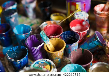 Multicolored plastic cans with paints. Artist workplace background. Old dirty Paints background. Colorful artist palette. Soft toned. Creativity, visual art concept. Art and craft. - stock photo