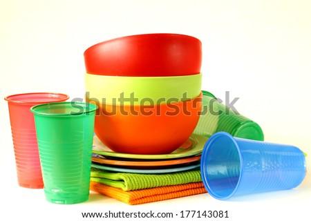 multicolored plastic tableware (cups, bowls, plates) - stock photo