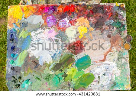 Multicolored Professional Palette With Freshly Caught Paint And Painter's Tools Outdoors