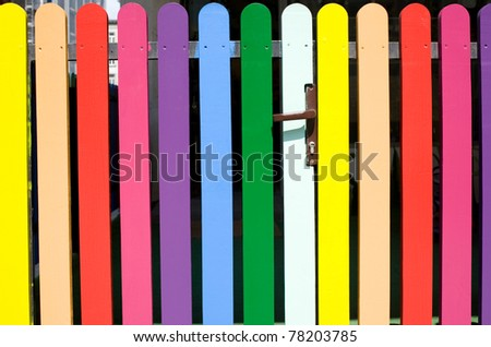 Multicolored rainbow picket fence with brown handle in open air in Warsaw, Poland. Horizontal orientation, nobody, front view detail.