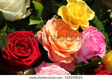 Multicolored roses in a flower arrangement - stock photo