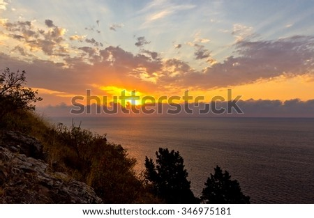 Multicolored seascape of Black sea with dramatic cloudy sky, Crimea. Top view with trees silhouettes on hill - stock photo