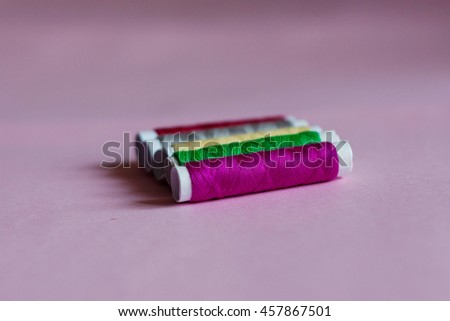 Multicolored sewing thread spools on pink pastel background - stock photo