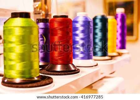 Multicolored sewing threads on spool; note shallow depth of field - stock photo