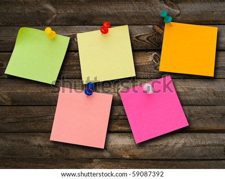 Multicolored stickers and notes and drawing pins at the wooden background