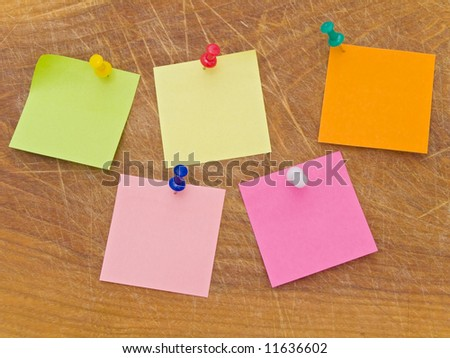 Multicolored stickers and notes and drawing pins at the wooden board