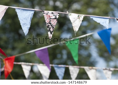 Multicolored summer Bunting flags hanging at an English garden party fete. - stock photo
