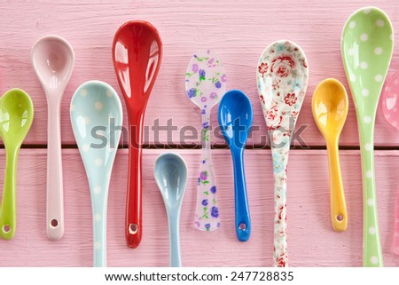 Multicolored tea spoons with various patterns on pink wooden boards - stock photo