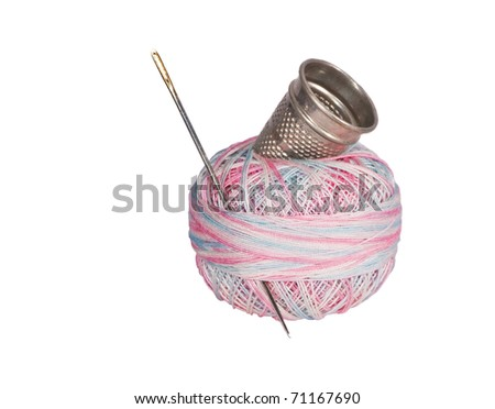 Multicolored thread with golden-eyed needle and metal thimble. - stock photo