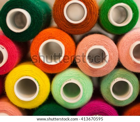 Multicolored  threads for sewing on a beige background - stock photo