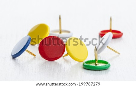 Multicolored thumbtacks on white desktop close up - stock photo