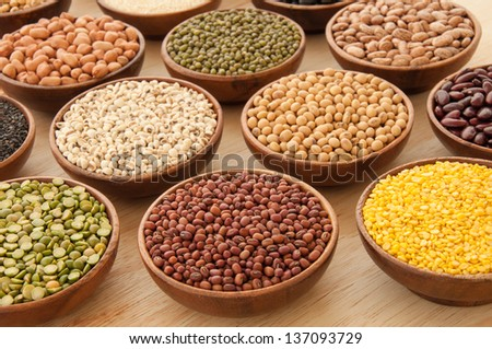 Multicolored types of grains in wooden bowls. - stock photo
