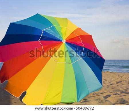 Multicolored umbrella on the beach - stock photo