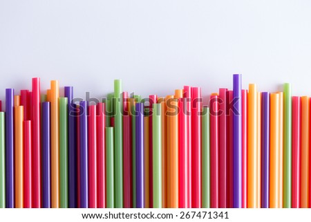 Multicolored vivid plastic drinking straws in a decorative background pattern two-thirds into the frame in an uneven line over a grey background with copy space for a celebration, holiday or festival - stock photo