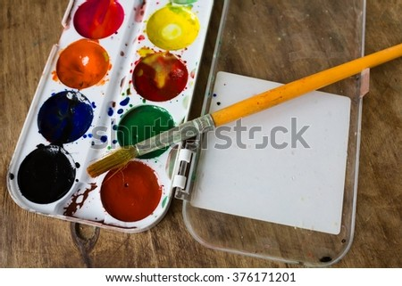Multicolored watercolor paints and brushes  - stock photo