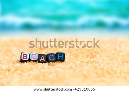 Multicolored word BEACH from black cubes in the sand on the background of beach and sea