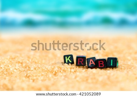 Multicolored word KRABI from black cubes in the sand on the background of beach and sea
