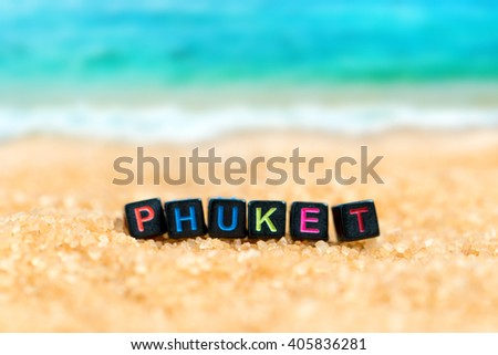 Multicolored word PHUKET from black cubes in the sand on the background of beach and sea
