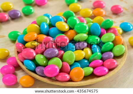 Multicolour chocolate candy on wooden plate - stock photo
